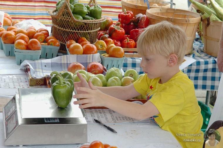 мальчик взвешивает овощи